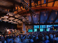 The facility's unique sliding glass panels capture the feeling of a summer night concert in a park.